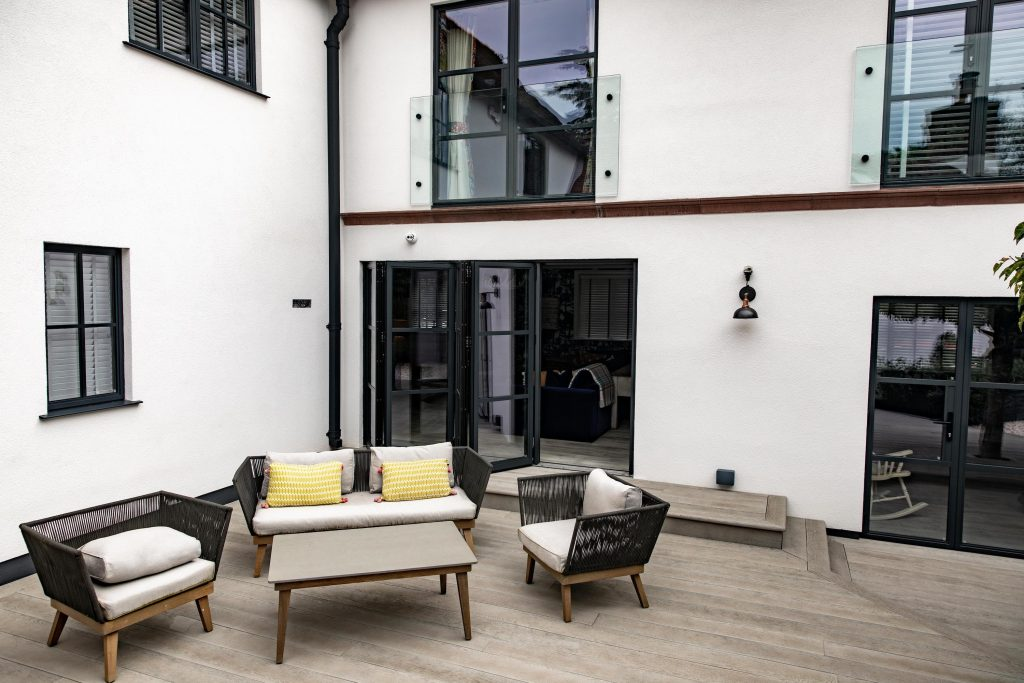 Garden sofas and chairs are shown against glass windows and doors are shown in the white walls of Woodbrook Place, Cheshire.