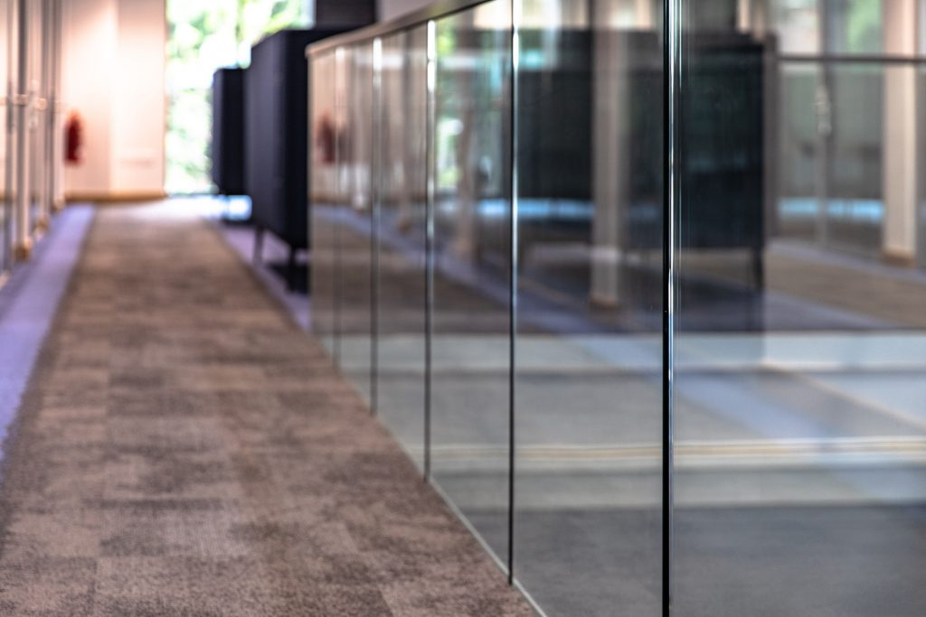 The frameless glass balustrade installed by Glass & Stainless at the University of Leicester Business School is shown along the corridor.