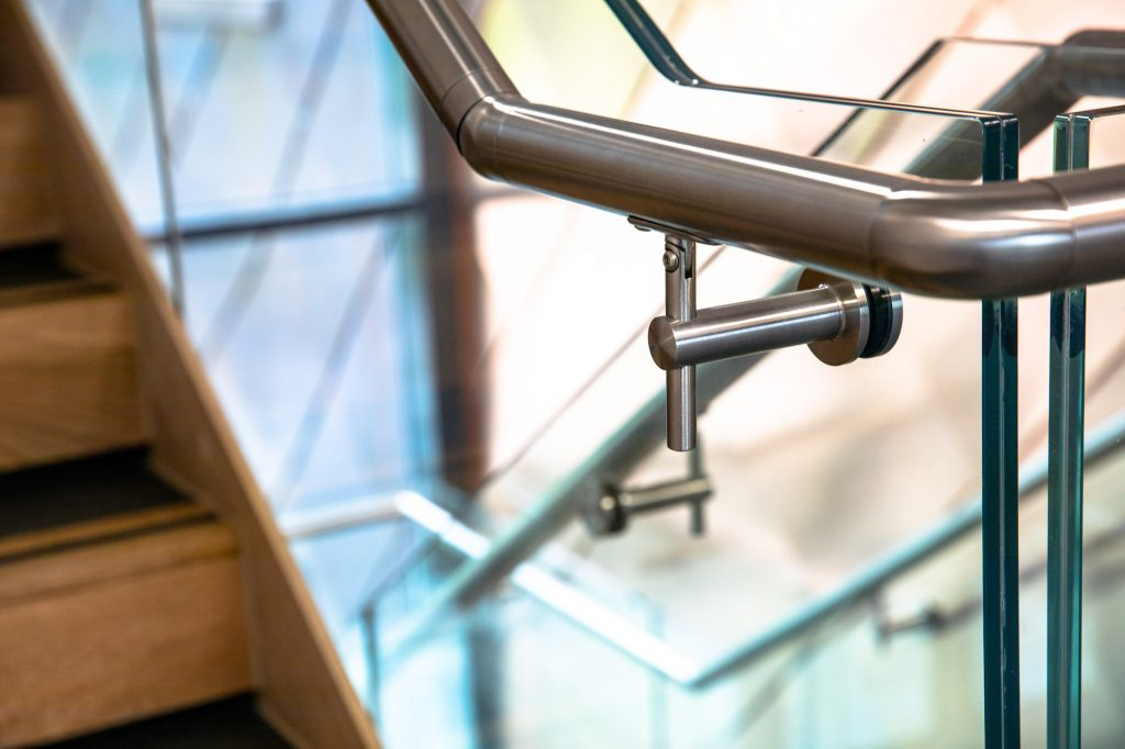 A handrail sits atop a frameless glass balustrade in the Business School at the University of Leicester.