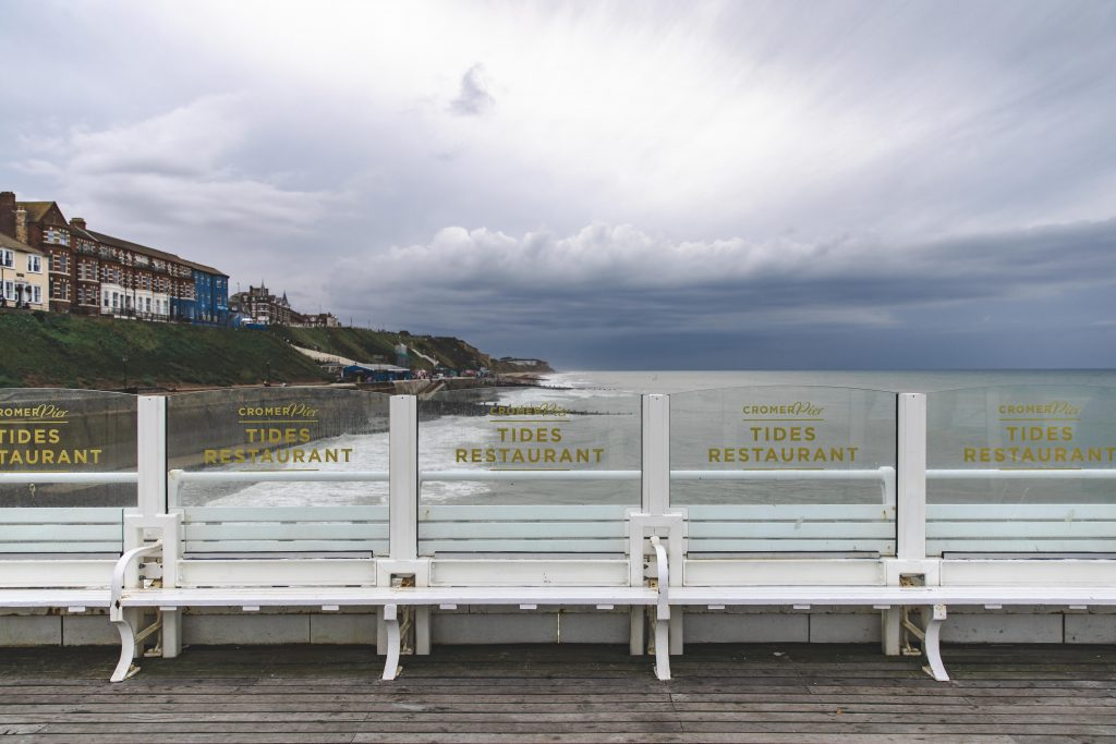 The glass panels of the pier with the Cromer logo showing against the beach, as created by Glass & Stainless.