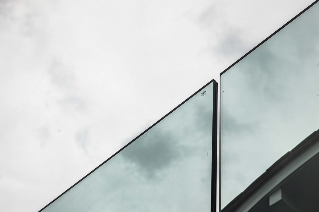 Two panels of the frameless glass are shown against a grey sky.