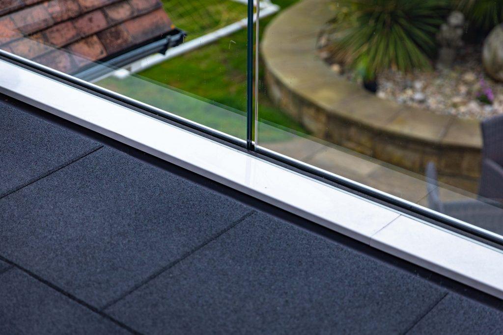 The black tile flooring of the external balcony is shown, and the runner and frameless glass panels of the balcony.