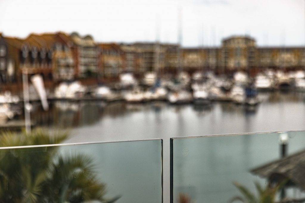 A close-focus shot of the frameless glass balustrades created by Glass & Stainless sits against the harbour in Eastbourne.
