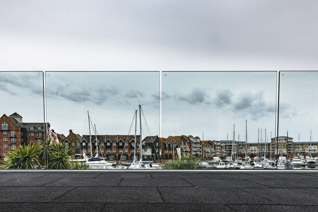 Frameless glass balustrade in Broad Reach, Eastbourne, showing the harbour.
