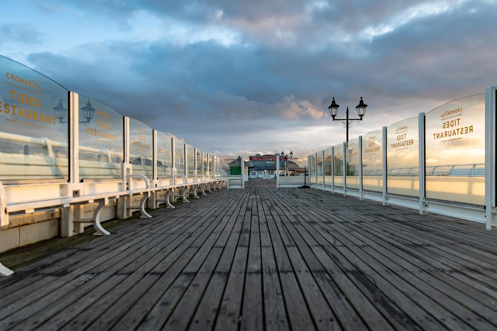 The Norfolk pier, lined with etched logo glass, is shown stretching into the sea.