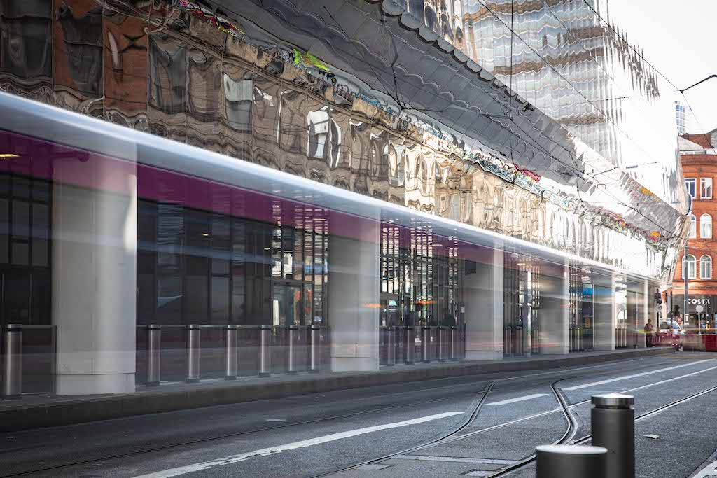 An image of the side of Birmingham New Street Station from the side, depicting glass walls and the mirrored roof.